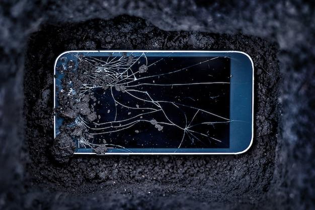 Konzept des telefons mit glasscherben in einem grab