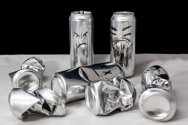 Konzept des terrorismus aluminiumdosen mit gezeichnetem emoji zerknitterte offene und leere wütende emoticons