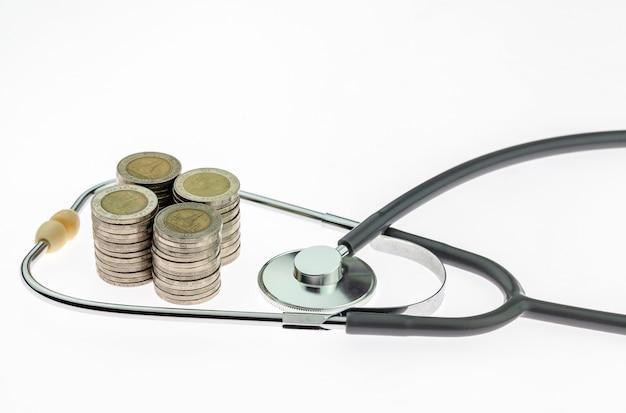Konzept des teuren gesundheitswesens mit münzen und stethoskop auf weißem hintergrund