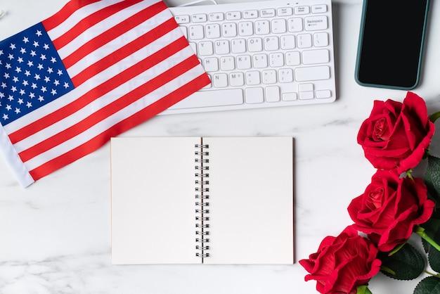 Konzept des us-unabhängigkeitstages am 4. juli oder am memorial day online-verkaufsfeier. nationalflagge und rotrose über marmortischhintergrund.