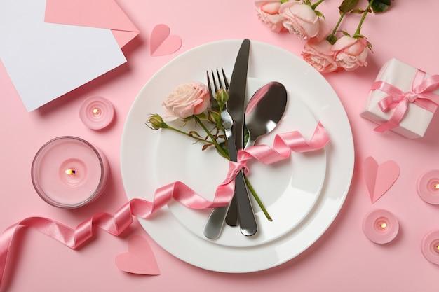 Konzept des valentinstags mit besteck, rosen und band auf rosa hintergrund