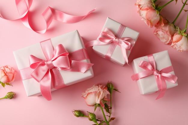 Konzept des valentinstags mit geschenkboxen und rosen auf rosa hintergrund