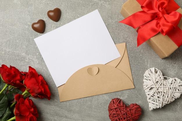 Konzept des valentinstags mit leerem umschlag auf grauem hintergrund
