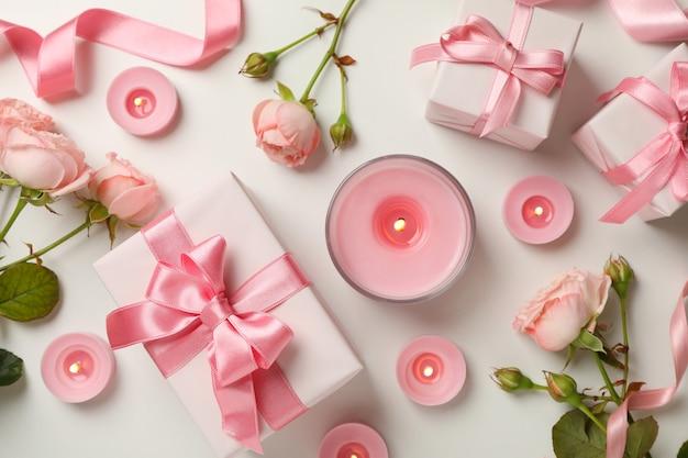Konzept des valentinstags mit rosen, geschenkboxen und kerzen auf weißem hintergrund