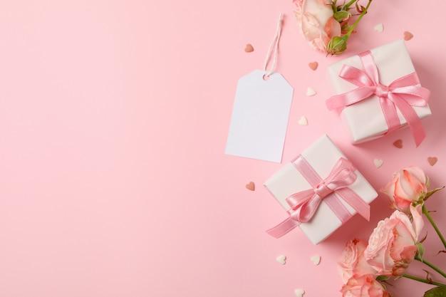 Konzept des valentinstags mit rosen und geschenkboxen auf rosa hintergrund