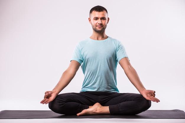 Konzept des yoga. hübscher mann, der yogaübung lokalisiert auf einem weißen hintergrund tut
