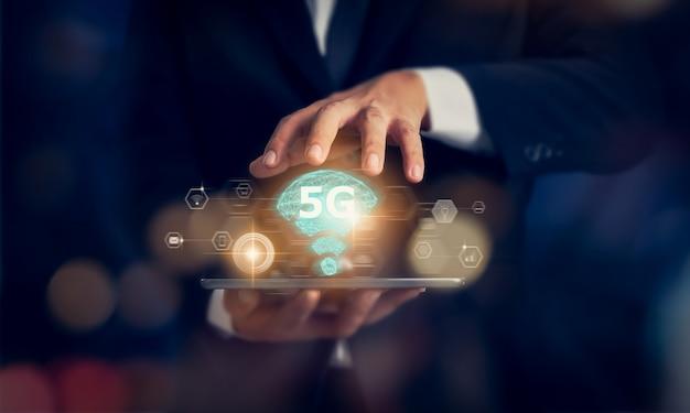 Konzept des zukünftigen netzes der technologie 5g, geschäftsmannhände, die tablette und hochgeschwindigkeitsnetzschirmschnittstelle der neuen generation halten. drahtlose systeme und internet der dinge (iot).