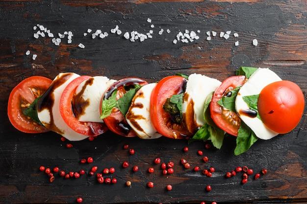 Konzept draufsicht auf frischen italienischen caprese-salat mit geschnittenen tomaten, mozzarella, grünem basilikum, geschnitten auf der horizontalen ansicht des alten küchentischs