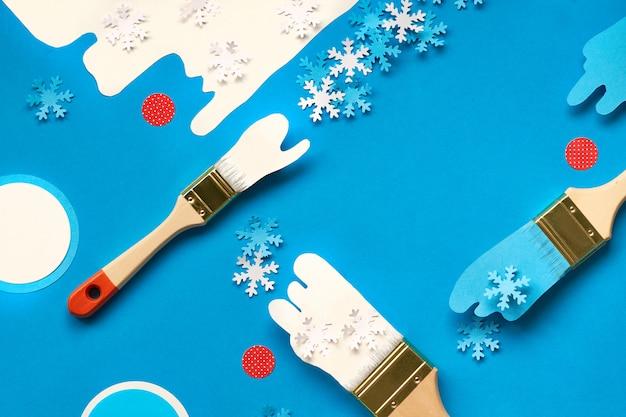 Konzept draufsicht flach lag winterhintergrund in blau und weiß mit bürsten, die mit papierschneeflocken geladen werden