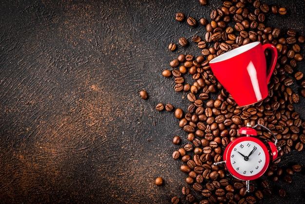 Konzept eines fröhlichen, guten starts in den tag, morgenkaffee. dunkler rostiger hintergrund mit kaffeebohnen, einem wecker und einem tasse kaffee. draufsichtkopienraum