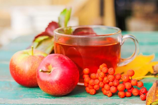 Konzept eines herbsttages. auf dem tisch steht eine glasschale tee, ein haufen rowan, äpfel und laub im freien
