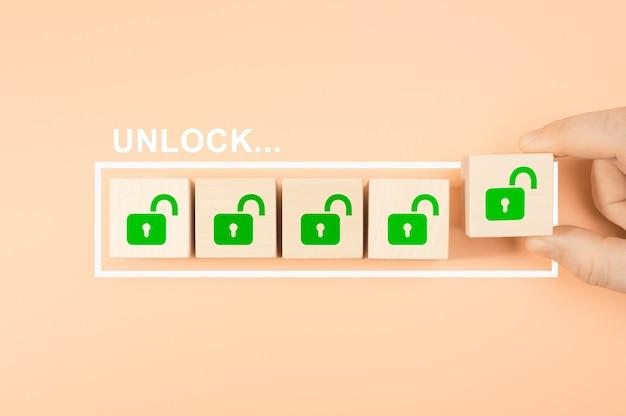 Konzept freischalten. hand, die hölzerne würfelblockform mit unlock-symbolzeichen auf fortschrittsbalken setzt, neue geschäftsmöglichkeiten freischalten