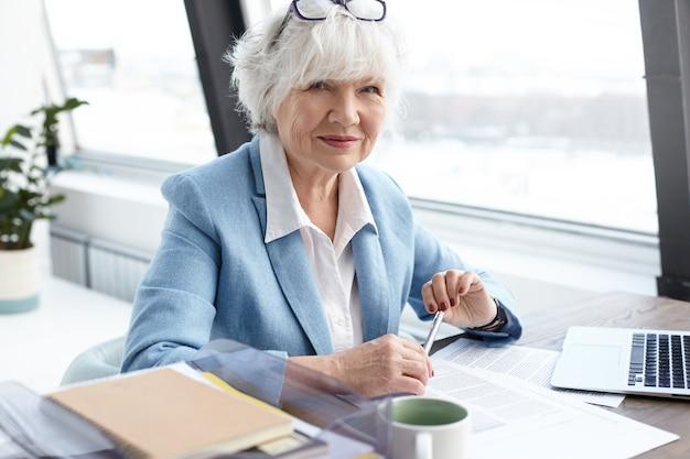 Konzept für alter, ruhestand, karriere und beschäftigung. porträt einer attraktiven kaukasischen geschäftsführerin in den sechzigern, die am schreibtisch vor einem offenen computer arbeitet, am fenster sitzt und ihren beruf genießt