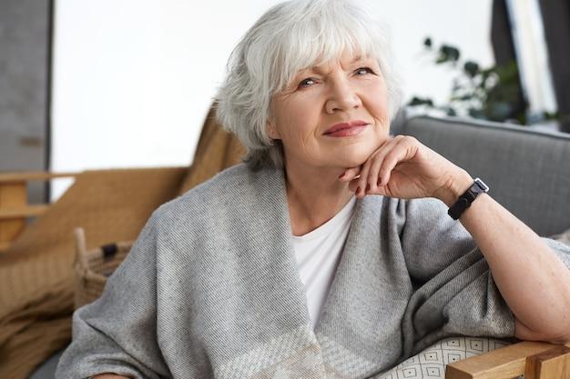 Konzept für alter, ruhestand und entspannung. glückliche fröhliche reife pensionierte frau, die mit strahlendem lächeln schaut, schönen wintertag genießt, auf couch sitzt, in weiten schal gewickelt, träumend