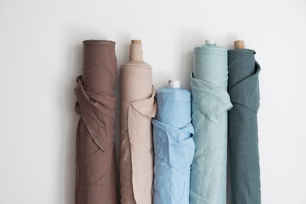 Konzept für den vorhangshop. leinenrollen in verschiedenen farben auf der hellen wand, selektives fokusbild