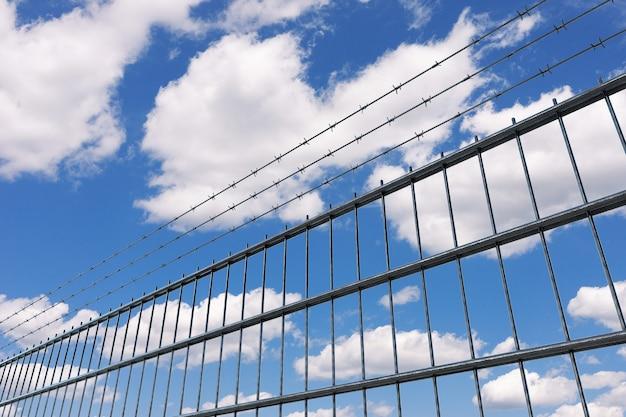 Konzept für eingeschränkte bereiche. metallzaun mit stacheldraht auf blauem himmelshintergrund. 3d-rendering