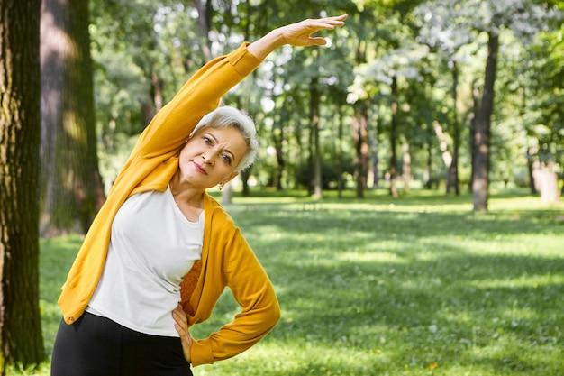 Konzept für energie, gesundheit, wohlbefinden und ruhestand. schöne sportliche ältere frau mit kurzen haaren, die seitenbeugung tun, arm ausgestreckt halten. pensionierte frau, die draußen im park oder im wald trainiert