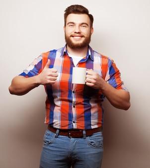 Konzept für essen, glück und menschen: junger bärtiger mann mit einer tasse kaffee vor grauem hintergrund