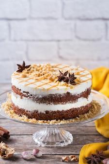 Konzept für essen und trinken. gesunder hausgemachter karottenkuchen mit walnüssen, nüssen und gewürzen auf einem rustikalen küchentisch. osterdessert