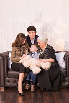 Konzept für familie, glück, generation und menschen - glückliche familie, die zu hause auf der couch sitzt