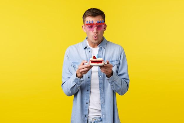 Konzept für feiern, feiertage und emotionen. verträumter, glücklicher, gutaussehender mann, der geburtstagskuchen wünscht, party hat, lustige sonnenbrillen trägt, brennende kerze für einen wahr gewordenen traum bläst.