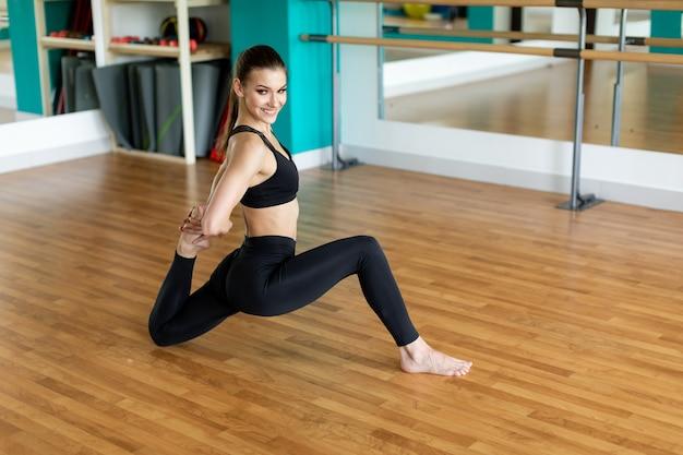 Konzept für fitness, sport und gesunden lebensstil - frau, die yoga-übung im studio macht.