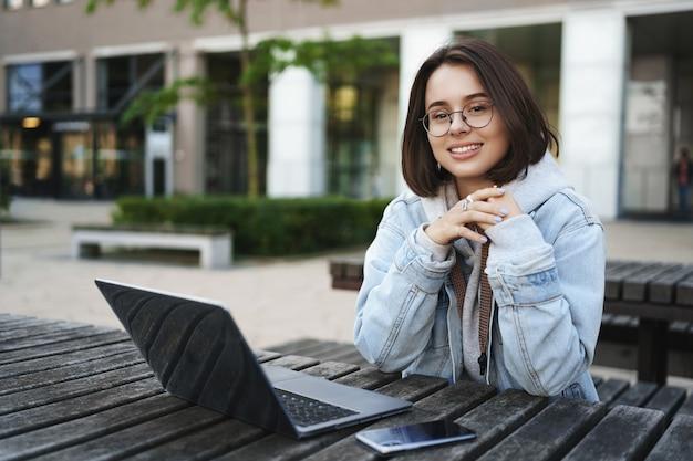 Konzept für freiberufler, menschen und bildung. fröhliches junges attraktives mädchen, das allein auf parkbank, universität sitzt, fernbedienung mit laptop, handy arbeitet, schaut mit erfreutem lächeln weg.