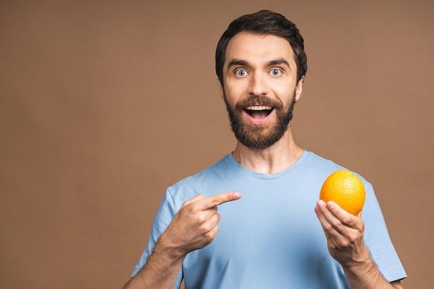 Konzept für gesunde ernährung und ernährung. porträt des jungen bärtigen lächelnden mannes, der eine orange frucht lokalisiert auf beigem hintergrund hält.