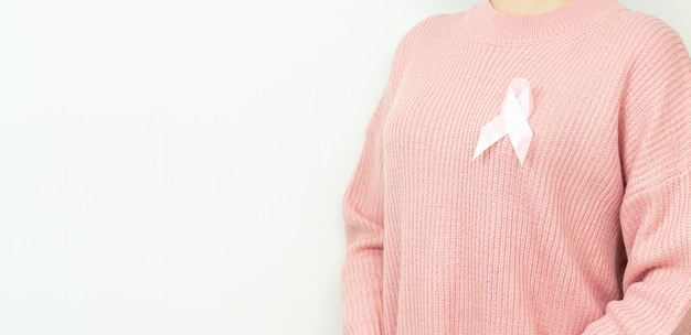 Konzept für gesundheitswesen, menschen, medizin und wohltätigkeit. frau im rosa strickpullover mit brustkrebs-bewusstseinsband auf weiß