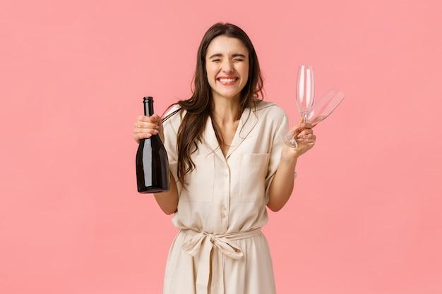Konzept für glück, feier und glückwunsch. charmante und aufgeregte, ekstatische kaukasische frau im kleid, enge augen und freudig lächelnd, eifrig offene flasche champagner und zusammen trinken