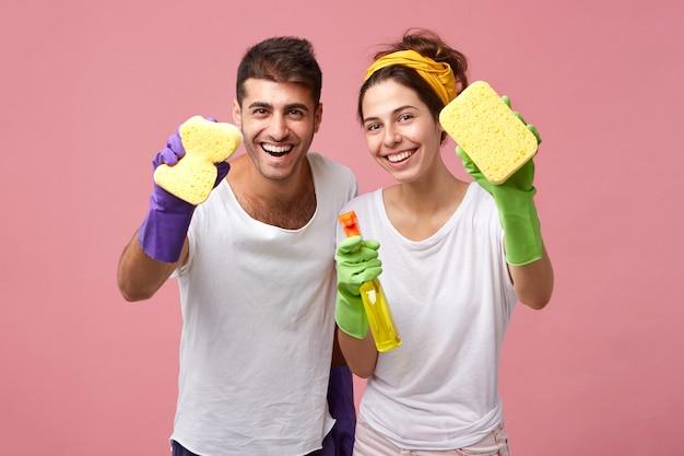 Konzept für haushalt, sauberkeit, hygiene und hausarbeit. glückliche kaukasische junge familie in schützenden gummihandschuhen, die waschmittel und lappen verwenden, während sie am wochenende zusammen in der küche aufräumen