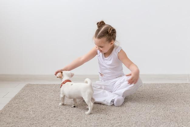 Konzept für hunde, haustiere und kinder - kleines mädchen, das mit süßem welpen auf dem boden spielt.