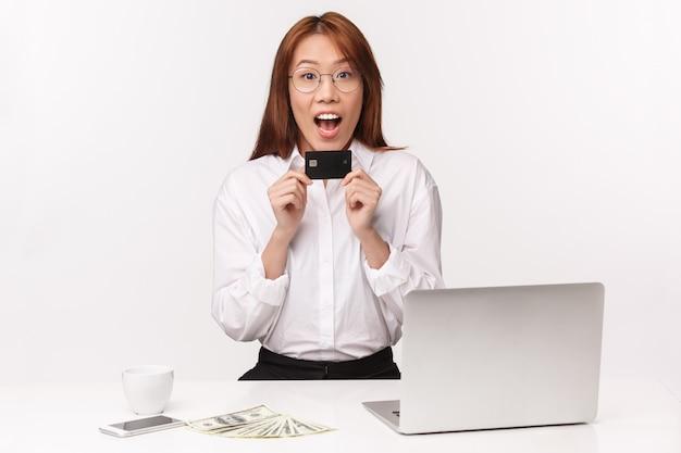 Konzept für karriere, arbeit und unternehmerinnen. fröhliche junge asiatische frau des nahaufnahmeporträts, die im büro mit laptop, geld sitzt, kreditkarte hält, amüsiert aussieht, ersten gehaltsscheck bekam