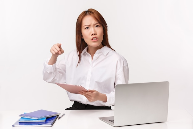 Konzept für karriere, arbeit und unternehmerinnen. nahaufnahmeporträt der enttäuschten verärgerten und unzufriedenen asiatischen frau, die schlechte ergebnisse des angestellten schimpft, tablette hält und auf person mit anklage zeigt