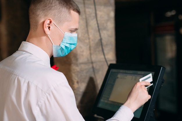 Konzept für kleinunternehmen, menschen und dienstleistungen. mann oder kellner in der medizinischen maske am schalter mit kasse, die an der bar oder im café arbeitet.