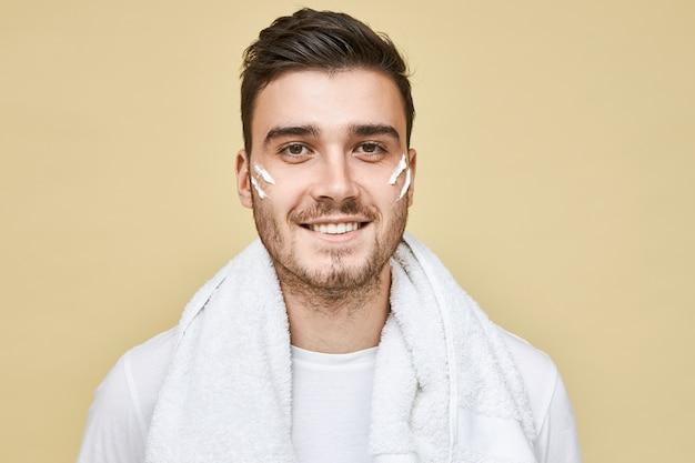 Konzept für männer, lifestyle, schönheit und hautpflege. bild des glücklichen jungen mannes mit der borste, die isoliert mit schaumstreifen auf seinen wangen und badetuch um den hals aufwirft, gesicht waschen und stoppeln rasieren