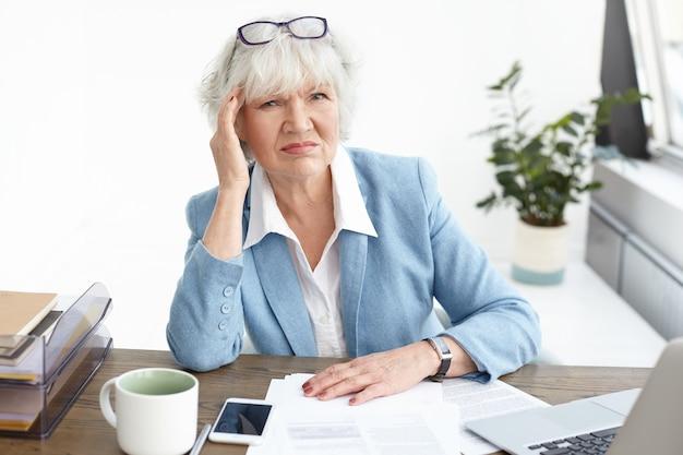 Konzept für menschen, alter, beruf, stress und gesundheit. bild einer missfallenen grauhaarigen geschäftsfrau, die die stirn runzelt, den kopf berührt, um schmerzen wegen kopfschmerzen zu lindern, zu viel arbeitet und papiere im büro studiert