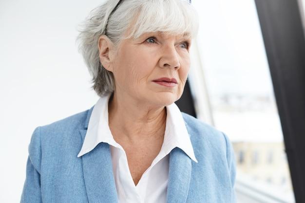Konzept für menschen, alter, lebensstil, mode und ruhestand. bild der eleganten modischen sechzigjährigen geschäftsfrau mit faltigem gesicht und weißem haar, das über geschäftsprobleme nachdenkt und am fenster aufwirft