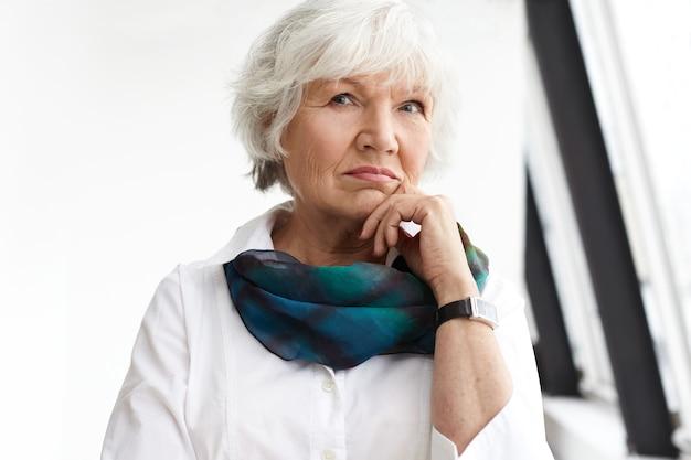 Konzept für menschen, alter, reife und lebensstil. porträt der stilvollen ernsthaften reifen geschäftsfrau mit kurzen weißen haaren, die das kinn berühren, nachdenklich aussehen und über geschäftspläne und -ideen nachdenken