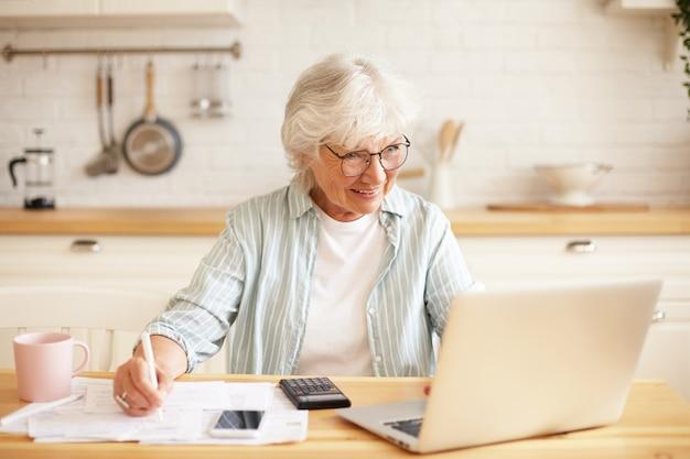 Konzept für menschen, alter, technologie und beruf. innenbild der attraktiven lächelnden grauhaarigen rentnerin, die laptop für fernarbeit verwendet, in der küche mit papieren sitzend, geld online verdienend