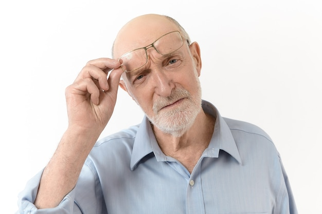 Konzept für menschen, altern, brillen, vision und optik. horizontales bild eines weitsichtigen älteren mannes mit weißem bart, der seine brille abnimmt und die stirn runzelt, um klar zu sehen, was vor ihm ist