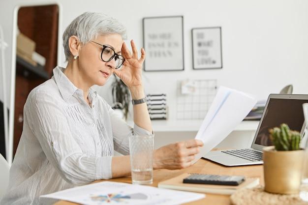 Konzept für menschen, altern, technologie und beruf. ernsthafte 50-jährige kaukasische frau, die stilvolle brillen und seidenhemd-lesevertrag trägt, während sie am schreibtisch arbeitet und vor offenem laptop sitzt