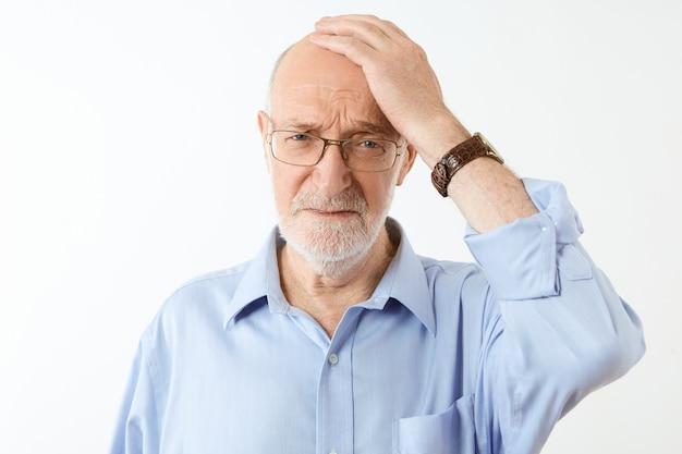 Konzept für menschen, altern und gesundheitsprobleme. frustrierter unglücklicher älterer kaukasischer mann mit grauem bart, der hand auf seinem kahlen kopf hält, der vergesslichen gesichtsausdruck hat und unter gedächtnisverlust leidet