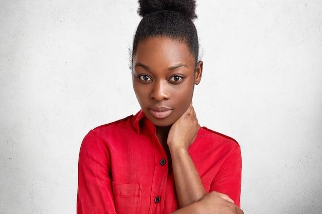 Konzept für menschen, ethnische zugehörigkeit und mimik. entzückende dunkelhäutige afrikanische schöne frau mit gesunder haut, posiert an der kamera mit selbstbewusstem blick