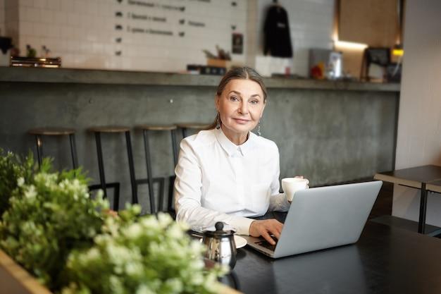 Konzept für menschen, freizeit und moderne technologien. bild der blauäugigen älteren dame, die am kaffeetisch vor offenem laptopcomputer sitzt, drahtlose internetverbindung benutzt und kaffee trinkt