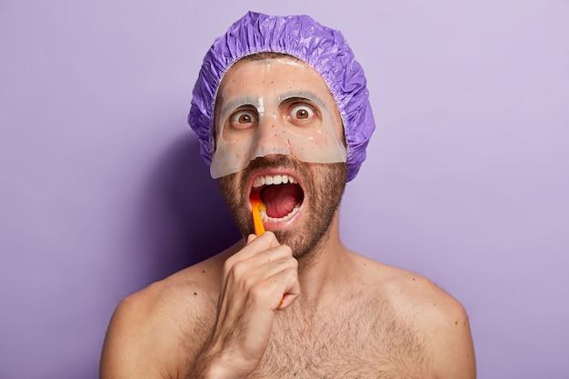 Konzept für menschen, hygiene und morgenroutine. nahaufnahme schuss des jungen mannes putzt zähne mit zahnbürste, hält mund offen, trägt badekappe, schönheitsmaske im gesicht