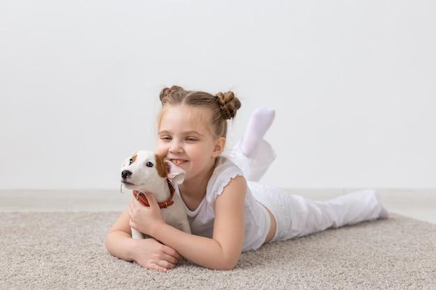 Konzept für menschen, kinder und haustiere - kleines kindermädchen, das mit dem süßen welpen jack russell terrier auf dem boden liegt