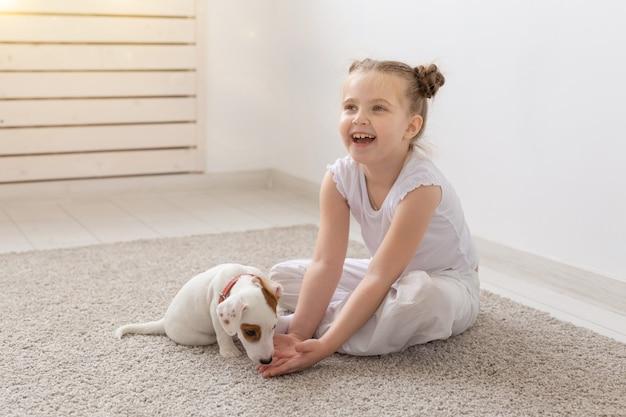 Konzept für menschen, kinder und haustiere - kleines kindermädchen, das mit süßem welpen auf dem boden sitzt und spielt