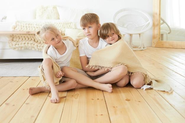Konzept für menschen, kindheit, familie, liebe und zusammengehörigkeit. süßes gemütliches bild von drei niedlichen kleinen kindergeschwistern, die zusammen auf holzboden sitzen, in decke gewickelt, einander umarmend