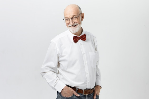 Konzept für menschen, lebensstil, alter und reife. hübscher fröhlicher älterer mann, der weißes hemd, rote fliege, blaue jeans und brille trägt, erfreuten blick, freudig lächelnd, erfolg feierend
